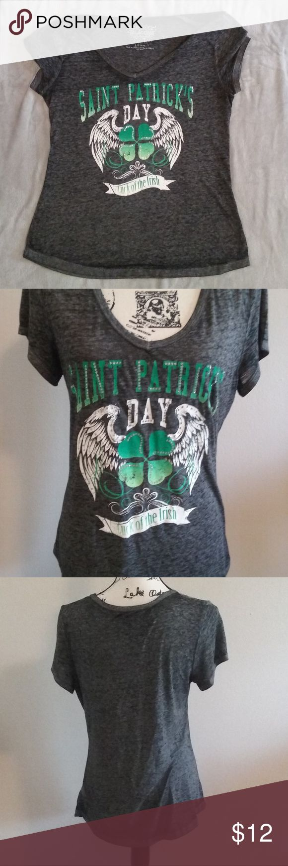 "St Patricks Day Irish Luck JRS Size L 11/13 Tshirt Nice and different gray St. Patrick's Day Luck of the Irish four leaf clover angel wings graphic t-shirt by Rocker Girl juniors size large 11/13, measures approximately 26.5"" long from back collar and 18"" underarm to underarm.  51% polyester and 49% cotton blend material.    Some shiny accents on lettering with distressed look graphic. Rocker Girl Tops Tees - Short Sleeve"