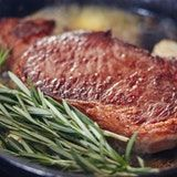 Flavor and baste the steaks: Carefully add the butter, garlic, and herbs to the pan. Flip the steaks once more. Tilt the pan so the butter pools on one side and use a large spoon to baste the butter over the steaks. Flip again and repeat. Begin checking the internal temperature of the steaks at 6 minutes total cook time for your preferred doneness. Medium rare is between 125 and 130°F.