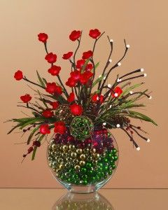 "Two are better than one in this arrangement. This design uses a floral lighted branch and a stick style lighted branch. Again the stylist uses colorful filler to secure the stems and conceal the power cord. Both the lighted stems are wired so they can be weaved between each other and the other faux stems to create this '""ready for the holidays"" look."