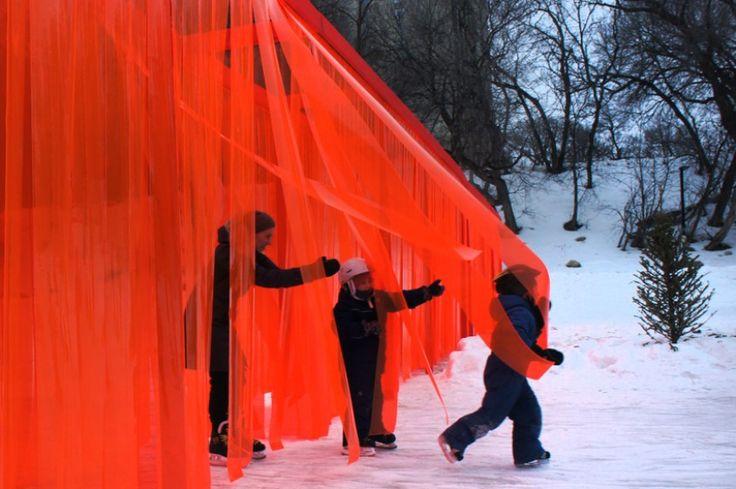 """Atelier ARI tarafından tasarlanan """"Açık Sınır"""", sınırları kapatmaktan hatta sınırlara duvarlar örmekten bahsedilen bugünlerde, bir çeşit protesto niteliğinde. Proje, mimar ve sanatçıları buz pateni pisti olarak kullanılan patika boyunca bir yerleştirme tasarlamaya davet eden 2017 Warming Huts Competition kapsamında tasarlanmış. Kırmızıya boyanmış ahşap bir iskelet üzerine yerleşen PVC şeritlerden oluşan geçirgen sınır, paten kayanların ve yayaların içinden rahatlıkla geçebilmesini sağlıyor…"""