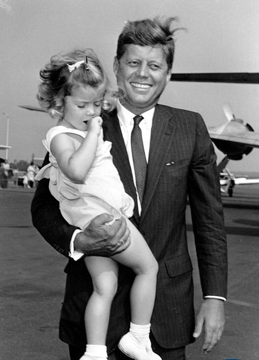 JFK and daughter Caroline shortly before he departs on a trip at the airport.