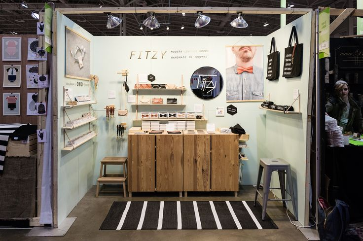 2015 One of a Kind Spring Show, @fitzyleather - lighting, lighting, lighting! Look how bright this booth is and how much it stands out! Vinyl on the back wall identifies the business and what they make. The open configuration is inviting to customers and shelving simply but effectively showcases products.