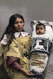 Mother and Baby  Description:Hand-colored photograph depicting a Native American mother holding her child in a cradleboard. This image is part of an exhibit about Native Americans prepared by Paul Vanderbilt, the first curator of photography at the Wisconsin Historical Society.