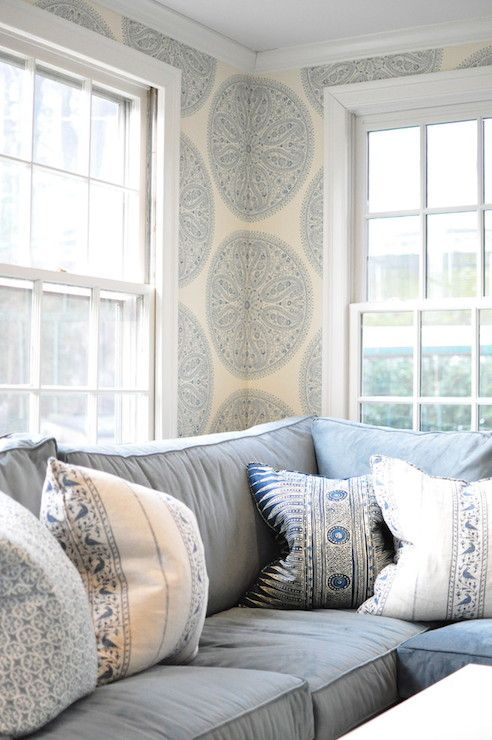 Blue and ivory living room with Paisley Circles Wallpaper by Caverley Wallpaper framing sash windows behind a blue sectional sofa topped with a collection of blue and ivory batik print pillows.