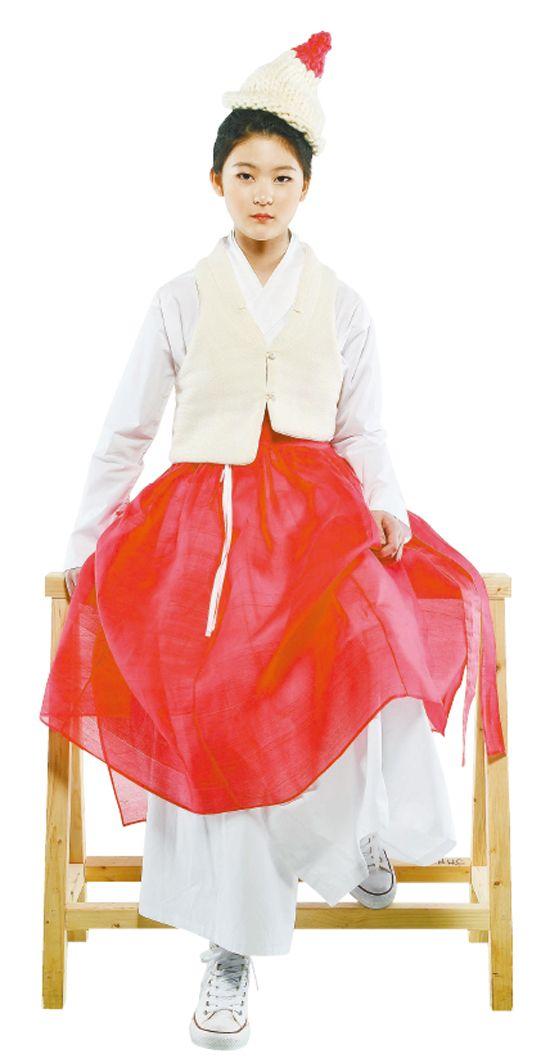 한복을 스타일리시하게 입는 첫 번째 방법은 여러 겹의 옷을 겹쳐 입는 레이어드 스타일. 브랜드 '차이킴'의 철릭 원피스는 레이어드를 하기 제격인 아이템이다. 차이킴은 김영진 디자이너가 한복을 평소에도 입을 수 있도록 재해석한 브랜드. 새하얀 철릭 원피스에 빨간색 공단 치마를 덧입고, 위에는 하얀 조끼를 매치했다. 요즘 유행하는 굵은 털실로 짠 털모자와 발목이 긴 스니커즈를 매치해 세련됨을 더했다. 옷과 모자는 차이킴, 스니커즈는 컨버스.