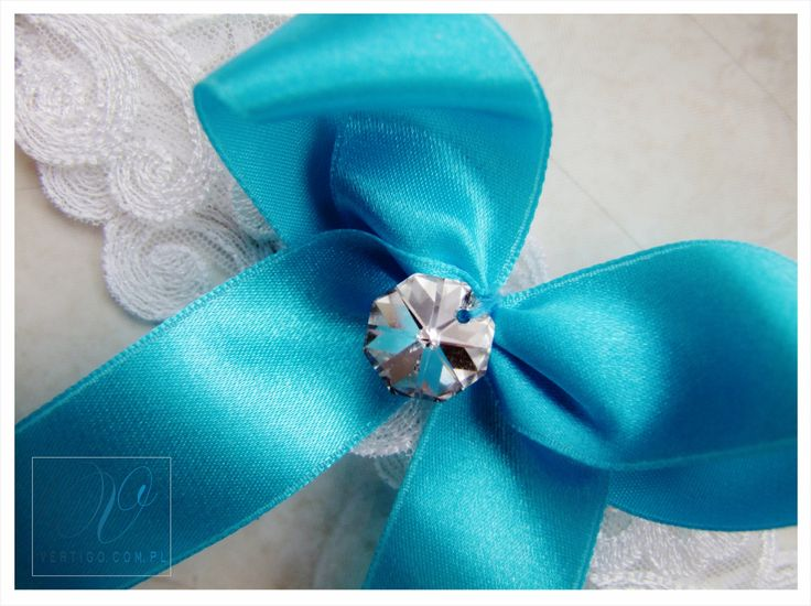 handmade wedding garter with lace, pearls, bow, feathers and swarovski crystals, source: www.vertigo.com.pl