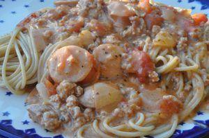 Familien får med garanti en ny livret, når du serverer denne pastaret med hakket svinekød, pølser og bacon. Smagen er mild og rund, med strejf af tomat og fløde