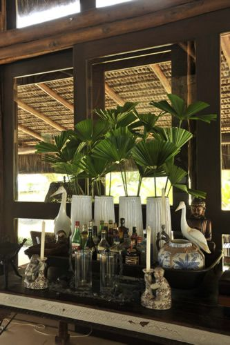 Vintage bar concept, small palms, candles, vintage serving trays, brass accent pieces, dark wood.