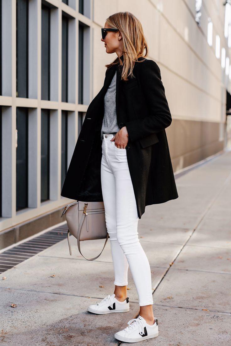 Blonde Frau trägt schwarzen Wollmantel grauen Pul…