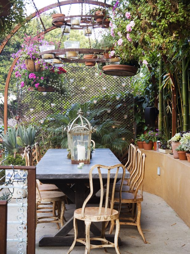 This outdoor chandelier of candles and hanging plants sets a playful mood.