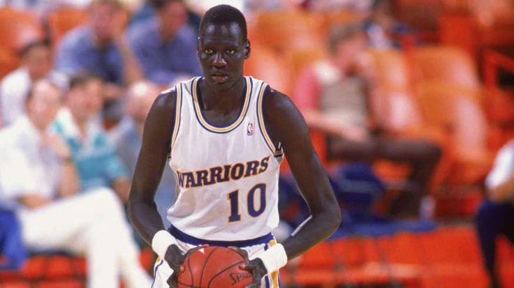 a baseball player holding a basketball: Manute Bol