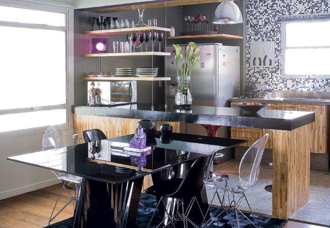 Com a demolição da parede entre a sala e a cozinha, os ambientes ficaram integrados. A bancada de concreto, com pintura de epóxi preto, e as prateleiras suspensas por cabos de aço dividem os espaços sem fechá-los. O projeto é assinado pelo Superlimão Studio  Maíra Acayaba / Casa e Jardim