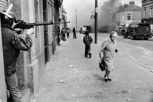© Chris Steele-Perkins, 1978, Falls road, Catholic West Belfast, Northern Ireland  Hijacked vehicle burns tin the background marking the anniversary of the British Policy of internment without trial.