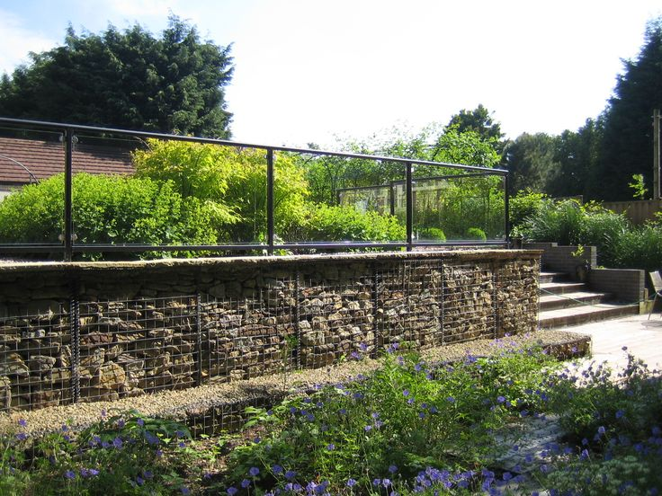 Stone filled gabion retaining walls support steel and
