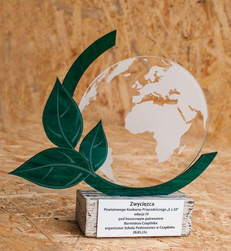 Statuetka na konkurs przyrodniczy w kształcie Ziemii., wykonana z postarzanego drewna, pleksi i laminatu grawerskiego.