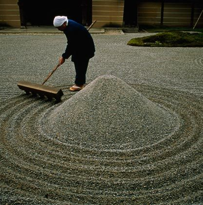 """A Zen Buddhist temple priest rakes gravel in a Kyoto garden. Karesansui, or """"dry gardens,"""" are abstract representations of natural landscapes in which stones, gravel, sand, and moss are used to depict mountains, rivers, and islands."""