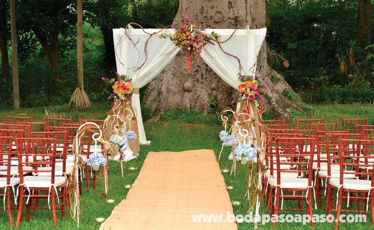 Gazebo elaborado con telas, decorado con lazas de yute y flores de diversos colores.