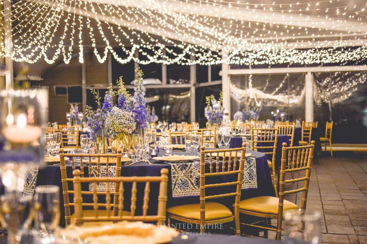 Majestic midnight blue with grand gold flatware and ornate charger plates formed the base to this beautiful styling. The smart use of on trend patterned napkins with a complementing stationary suite of menu, table number and individual place cards cleverly tucked into each guest golden fork. This setting sat under a canopy of warm white fairylights that shone brightly above guests tables laden with stunning florals and candlelight.  Youtube: www.youtube.com/watch?v=xfwLgKtlLyE  Enchanted…