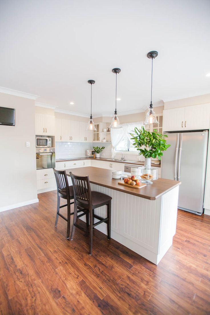 the kitchen maintains the country charm of the exterior of the home with use of heritage kitchen cupboard door