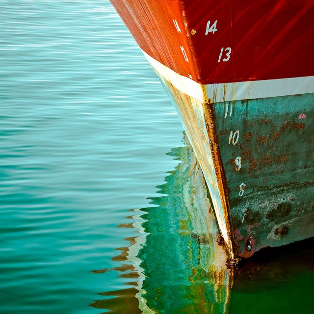 The hull of the boat has an old paint job on it consisting of 3 colors: 1) BOTTOM of hull is a sea blue/green paint; 2) above that a thin white stripe of white paint; 3) the highest part of the hull is a burnt orange/red mixture of paint.