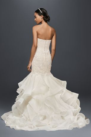 "The structured organza skirt of this trumpet wedding dress provides a stunning focal point. Embellished with over 3,000 beads and sequins, the baroque lace bodice gleams softly, while creating a long, graceful silhouette.   Oleg Cassini, a David's Bridal exclusive  Polyester  65"" Chapel train  Back zipper; fully lined  Dry clean  Imported  Also available in petite and plus size  Extendedl-length train style XTCWG769"