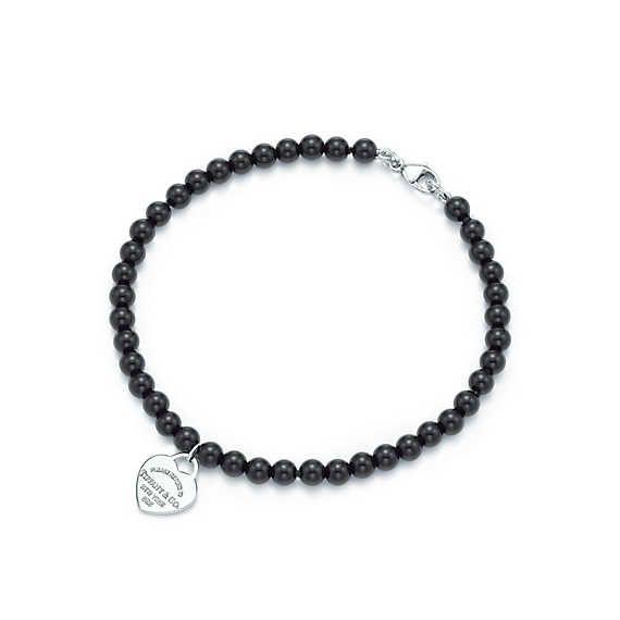 Return to Tiffany™ mini heart tag in silver on a black onyx bead bracelet.