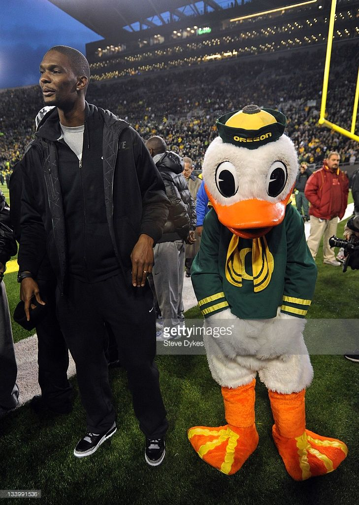Chris Bosh stands next to 'Puddles', the Oregon Duck mascot, on the sidelines before the game between the Oregon Ducks and the USC Trojans at Autzen Stadium on November 19, 2011 in Eugene, Oregon.