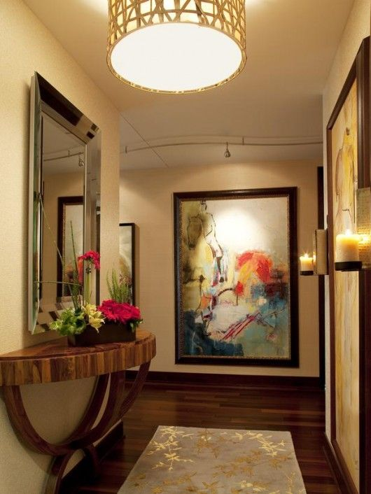 Warm Lighting. Candle sconces and a drum-shaped light fixture cast soft, warm light in this entryway. Track lighting is used to draw attention to the exquisite artwork displayed in the space.