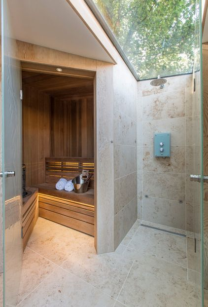 A glass roof panel arches over the walk-in shower, which is next to the cedar-paneled sauna.