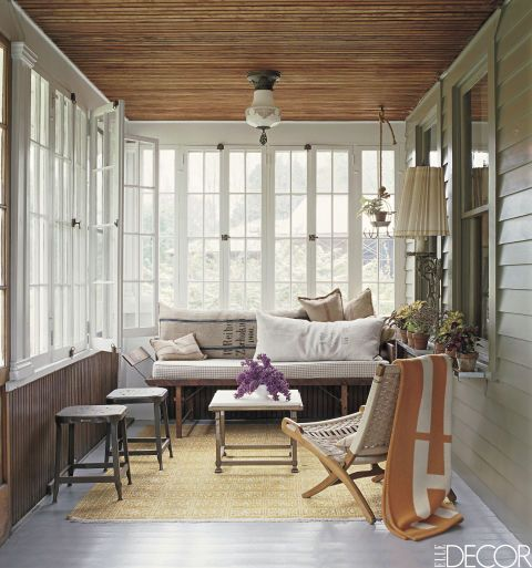 Designer Dale Saylor and stylist Joe Williamson furnished the porch of their 1928 Craftsman cottage in Columbia County, New York, with a 1950s Czech rope-and-wood folding chair found on eBay and industrial metal stools. The 19th-century folding bench is topped with pillows made from grain sacks. The throw is by Hermès, and the rug is from a Manhattan flea market.