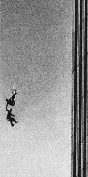 """""""This photograph intrigues me so much! Why isn't this the most famous photo from 9/11 instead of the falling man? Isn't two people holding hands after jumping, more significant than 1 man? It makes me wonder what the story is behind this photo... were they friends or lovers, or just strangers who were too afraid to jump alone? It shows that people need a helping hand even in their final moments!"""""""