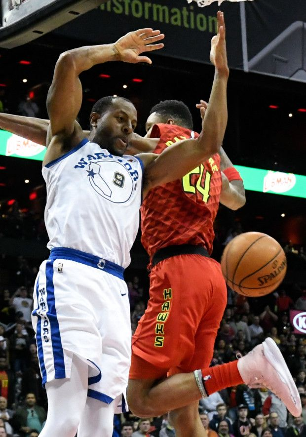 Golden State Warriors forward Andre Iguodala (9) dunks against Atlanta Hawks guard Kent Bazemore after stealing the ball and bringing it downcourt during the closing moments of an NBA basketball game Friday, March 2, 2018, in Atlanta. (AP Photo/John Amis)