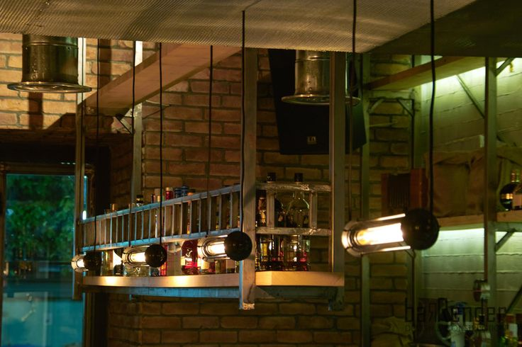 Industrial style bottle rack in front of bar and vintage pendant luminaires with edison lamps - Rag Doll Post modern bar in Athens.
