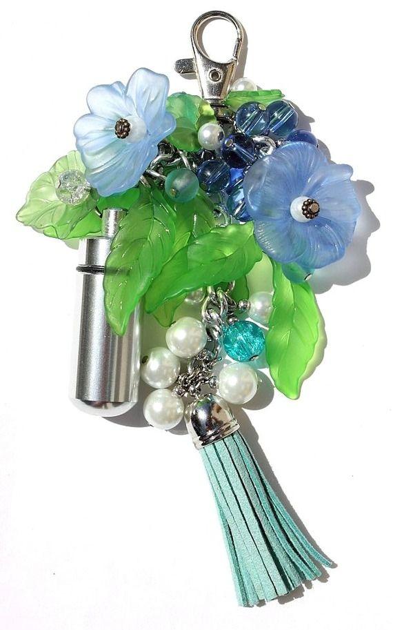 Bijou de sac composé d'un pilulier orné de fleurs bleues et feuilles en lucite et de perles en verre