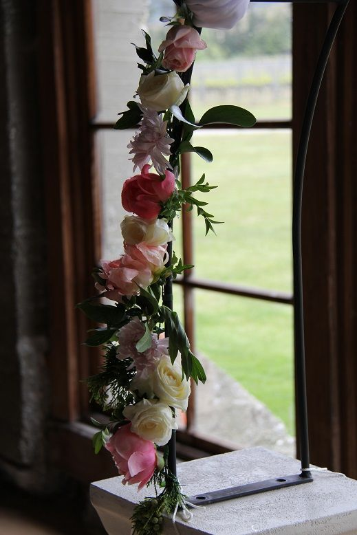 Roses and paeonies lift the harshness of a metal arch  http://www.wanakaweddingflowers.co.nz/