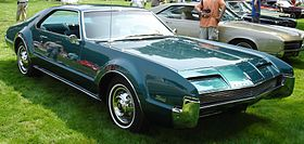 1966 Oldsmobile Toronado...just like this one.  Front wheel drive, flat floor boards, roomy. Quite a ride.