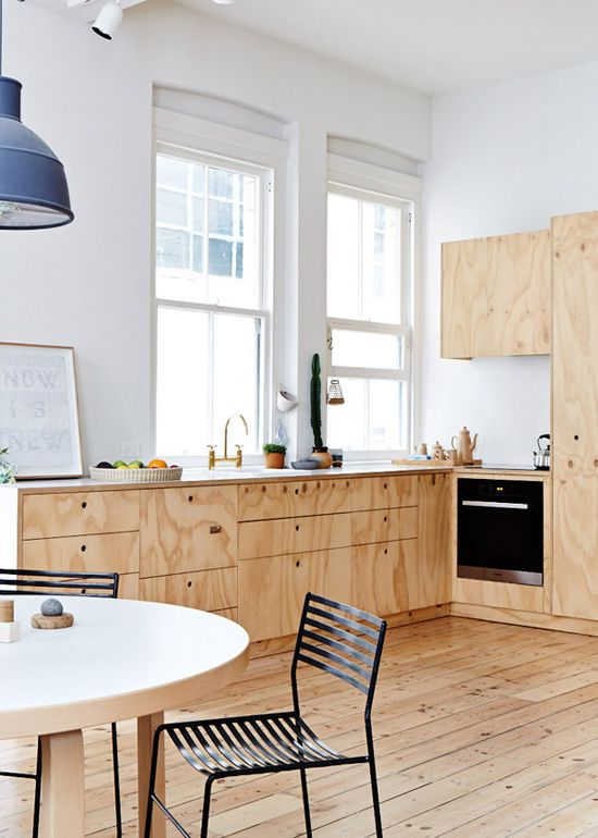 Love the raw wood cabinets with beautiful wood grain, raw wood floor, blue pendant light.