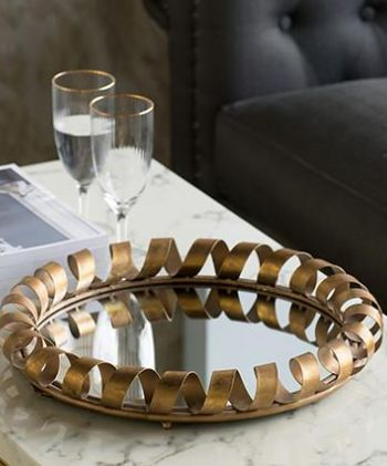 Anton Gold Mirror - used as a tray! Our Round Bronze Spiral Mirror is industrial meets luxe home decor. Its key feature is its bronze ribboned detailing along its edges. This is a signature piece for a room with bare walls or interiors styled with metallic decor. $130RRP AUD. For wholesale enquiries, email: info@philbee.com.au