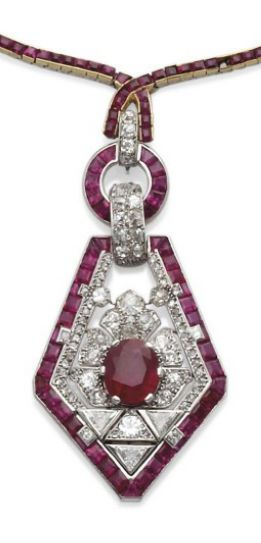PENDANT ART DECO RUBY AND DIAMOND, RUBY AND CHAIN ​​BY CARTIER Formed a circle holding calibrated ruby pendants in a geometric pattern of diamonds old cut and trimmed in pink and ruby ​​calibrated surrounding an oval ruby, platinum setting, French punch, 53.8 gr., With a chain set with rubies calibrated (one missing), 51 cm., frame gold and platinum, circa 1925.