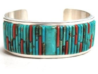 """Details  Navajo artist Veronica Benally has a very eye-catching style. This bracelet combines row after row of turquoise and coral inlay pieces, a spectacular colorful puzzle. The stones are set on a wide sterling cuff that has great weight and is finished with a unique stamp pattern down each end.   Artist:  Benally, Veronica  Tribal Affiliation:  Navajo  Main Stone:  Multi-Stone  Metal:  Sterling Silver  Style:  No  Size:  5 7/8"""" Circumference, 1 1/4"""" Opening, 1"""" Width  Age:  New"""