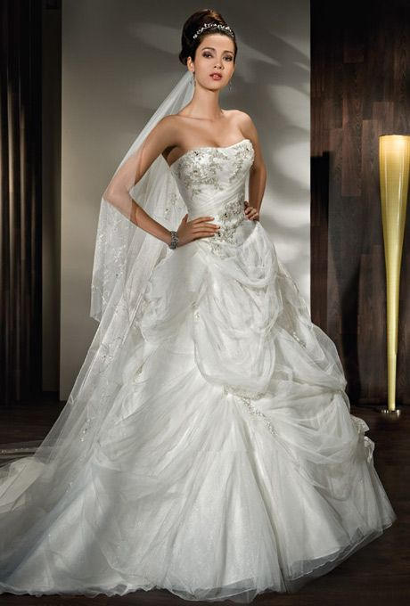 Brides: Demetrios - Young Sophisticates. Strapless beaded tulle ball gown with a ruched wrap bodice and lace-up back. Gown features bustles and scattered beading throughout skirt and train.