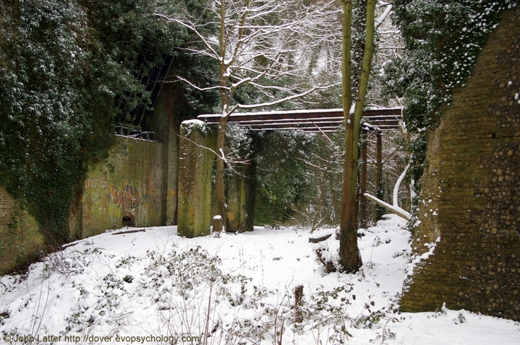 Victorian Inner Bridge Ruins under Snow, North Entrance, Western Heights, Dover, Kent, England, UK. Classic view of the drawbridge (left) and bridge combination that spans the South Tenaille Moat; the Tenaille, a monolithic block, is the brickwork on the right, road tunnel on left behind drawbridge beams. Part of Dover's Forgotten Fortress, a defense system begun during the Napoleonic Wars then continued in mid-Victorian era. Winter 2010 (February). See…