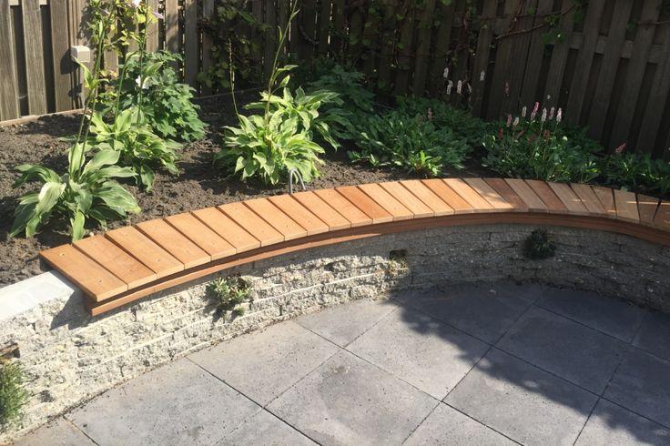 Ronde stapelmuur van gebroken betontegels met hardhouten zitrand. Ontwerp: Vicas Tuinontwerpen.