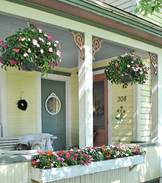 Hanging baskets on a summer farmhouse porch - porch decorating ideas