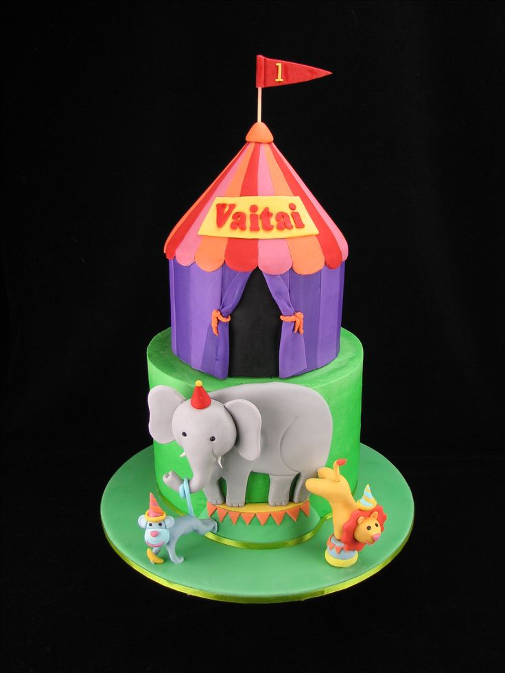 A chocolate mud cake circus tent covered in fondant sitting on top of a rainbow layer cake with smooth buttercream finish. The tent and circus animals matched the birthday invitations.