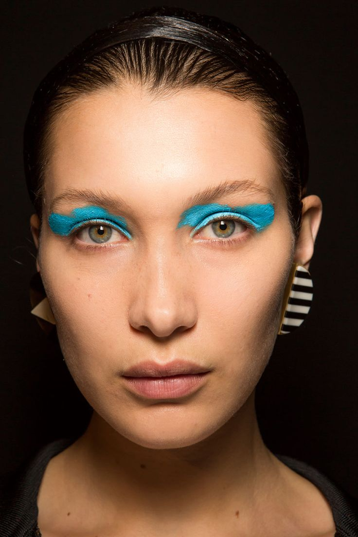 "Makeup artist Lucia Pieroni created ""sporty tribal"" eyes backstage by drawing on M.A.C. Acrylic Paint (she alternated between white, yellow, neon blue and navy) with her fingers in two soft, sweeping motions.    - HarpersBAZAAR.com"