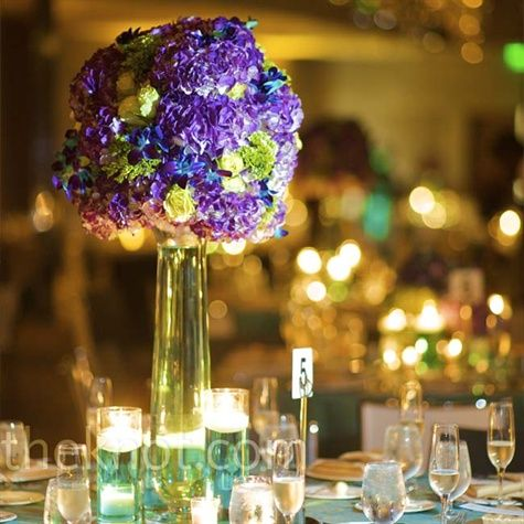 Tall vases were filled with teal-colored water and topped with an assortment of blue dendrobium orchids, purple hydrangeas, green mini hydrangeas, and jade roses. Shorter centerpieces decorated every other table and all sat atop mirrored mats among water-...