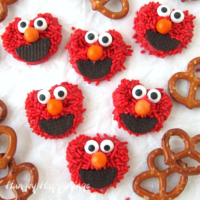 Elmo Pretzels make cute Sesame Street party food. Each mini pretzel twist coated in red candy melts and red sprinkles is decorated with a big chocolate cookie mouth, an orange candy nose, and cute candy eyes. Kids of all ages will fall in love with these easy-to-make Elmo desserts.