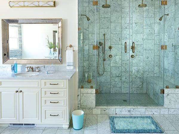 The generously sized shower in this Covington, Louisiana master bathroom has walls of the same Carrara marble that covers the floors. Nearby, beaded mirrors and criss-cross wall lights hang above each vanity. (Photo: Laurey W Glenn)