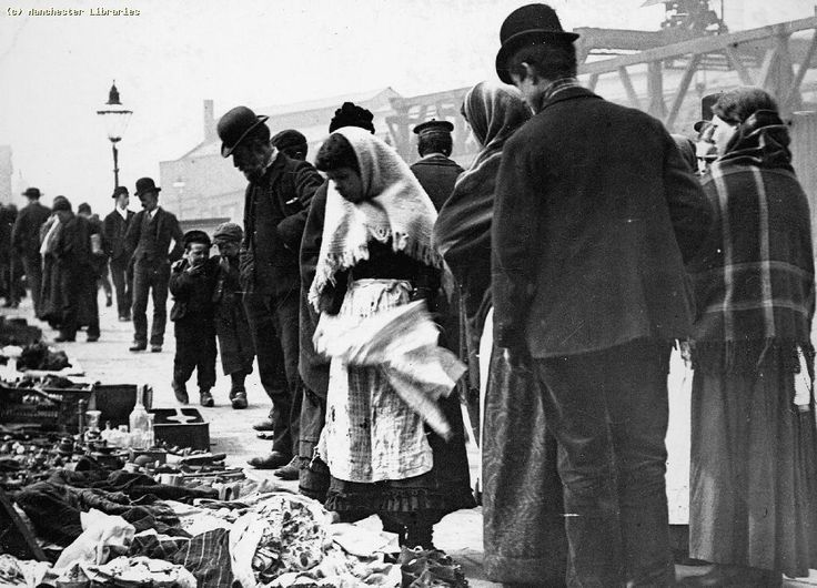 Picking old clothing at a slum in Salford, U.K. The poorest people could only afford clothes to avoid indecency, the colour/style was never an option. It's hard to imagine living that way now.